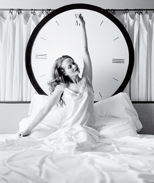 Black and white photograph of woman stretching in bed in front of a giant clock