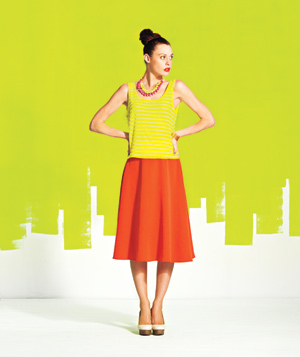 Model wearing neon green shirt and neon orange skirt