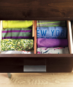 T-shirts rolled neatly into a drawer