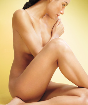 Nude model sitting with legs crossed