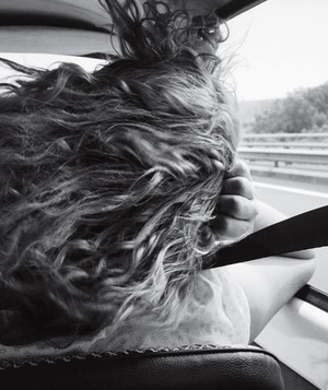 Woman sitting in car with her hair blowing in the wind