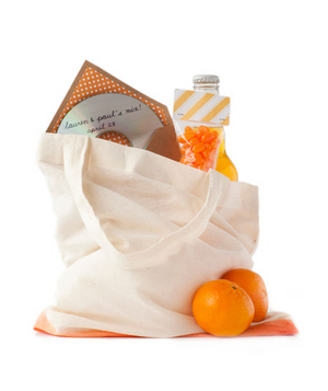 Canvas bag filled with oranges, a cd, soda and candy
