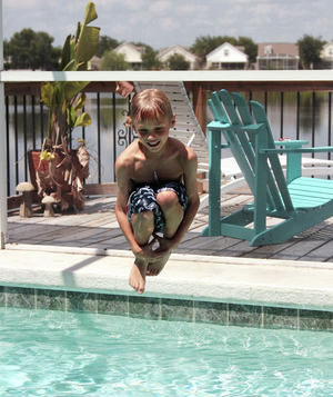 Boy doing a cannonball into a pool