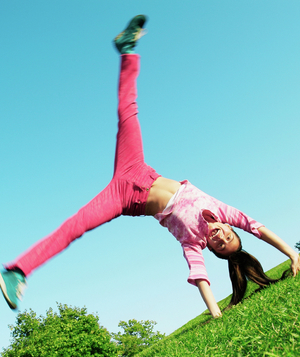 Girl doing cartwheel on the grass