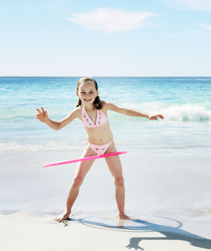 Two girls hula hooping on the beach
