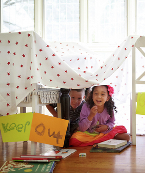 Boy and girl in kitchen table fort