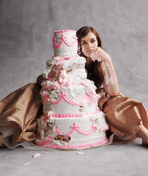 Model sitting behind a tiered cake looking sad