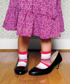 Little girl playing dress up in woman's heels