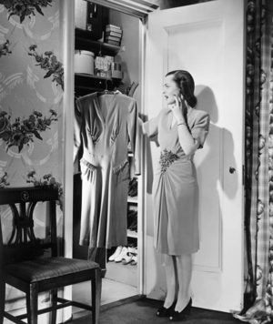 Woman standing outside closet with dress in hand