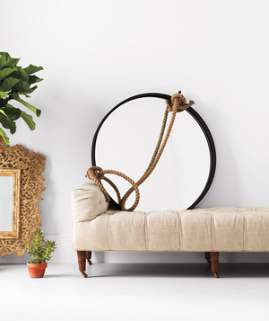 Iron and rope mirror sitting on a linen settee