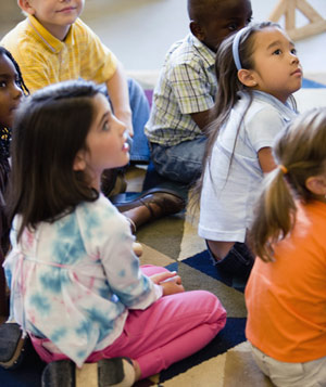 Children in classroom sitting on floor