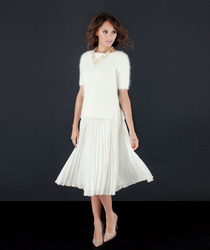 Model wearing white pleated skirt