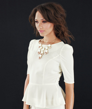Model wearing acrylic bauble necklace and peplum top