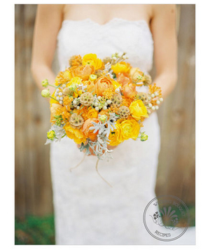 Yellow bouquet filled with roses, billy balls, and ranunculus