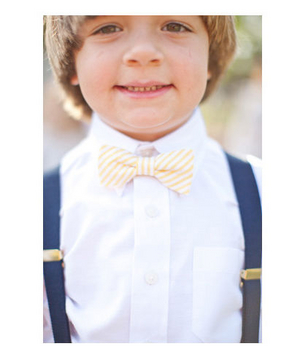 Little boy wearing a striped yellow bow tie and blue suspenders