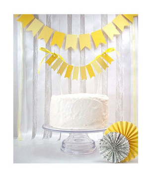 Yellow paper garlands hanging above a wedding cake
