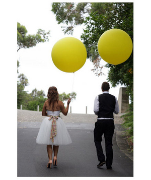 Bride and groom carrying oversized yellow balloons