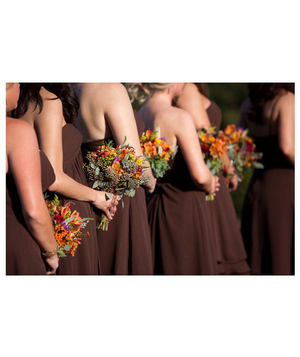 Bridesmaids in brown holding bouquets of multicolored wildflowers
