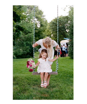 Flower girl sitting on a swing