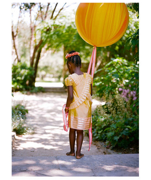 Little girl in yellow dress holding a large balloon