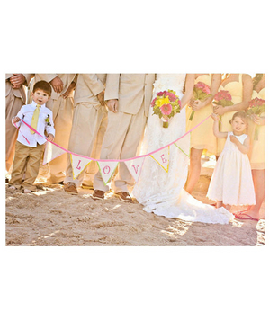 Flower girl and ring bearer holding love banner