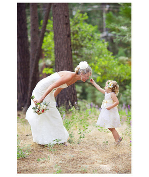 Bride and flower girl in the woods