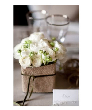 White ranunculus in a burlap-wrapped vase with velvet ribbon