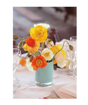 Blue vessel holding orange and yellow centerpiece