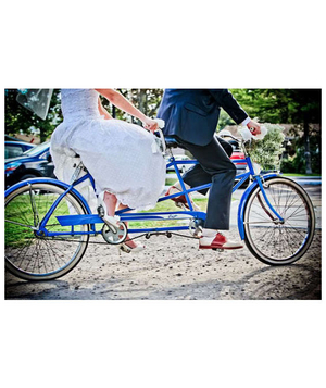 Bride and groom riding blue tandem bicycle