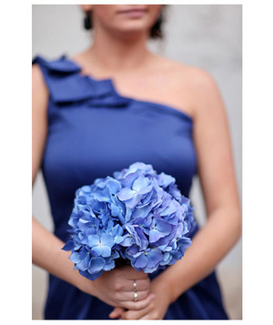 Bridesmaid wearing blue dress holding blue bouquet