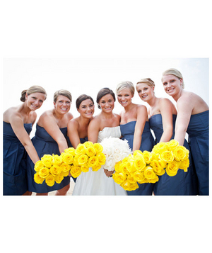 Bridesmaids wearing navy dresses and holding yellow bouquets