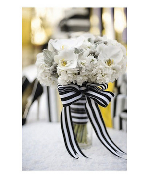 White bouquet tied with black and white striped ribbon
