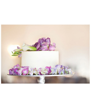 Wedding cake topped with real purple flowers