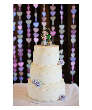Wedding cake with purple sugar flowers and hanging hearts