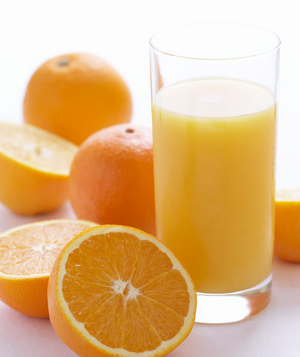 Fresh oranges and a glass of orange juice