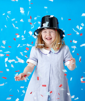 Birthday party guest wearing a magician's hat and standing in confetti