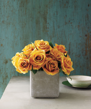 Cluster of yellow roses in a short vase