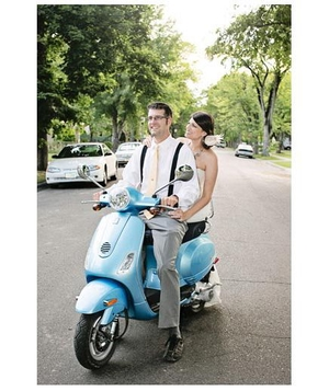 Newlyweds riding a blue moped