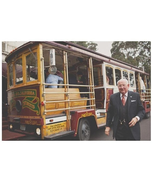 Old man in a suit standing outside of a street trolley