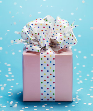 Pink present with white bow and confetti