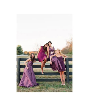 Bridesmaids sitting on a wooden fence