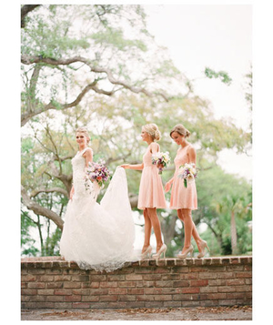 Bride and bridesmaids walking on a short stone wall