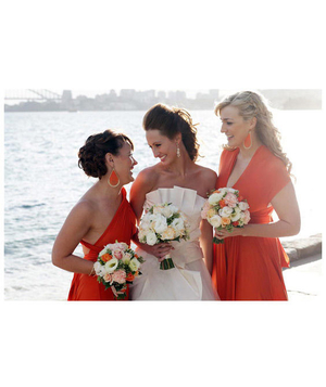 Two bridesmaids smiling with bride