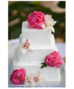 White cake topped with pink peonies