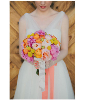 Bride holding a bouquet of pink peonies, orange ranunculus, and yellow billy balls