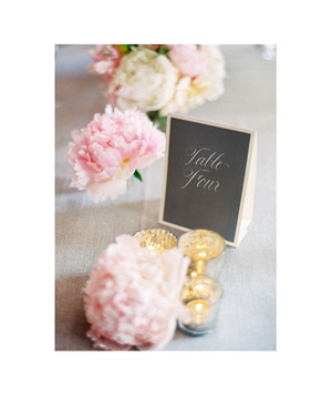 Peonies scattered on a table at a wedding reception