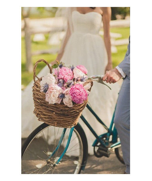 Bride and groom with a bicycle basket full of peonies