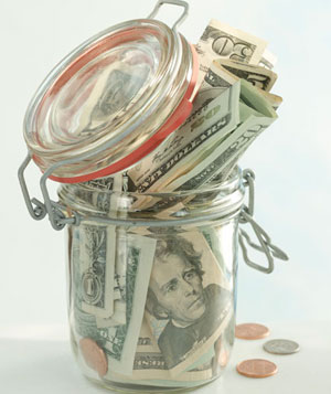 Money stuffed into a glass jar