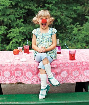 Smiling girl sitting on picnic table with big red clown nose