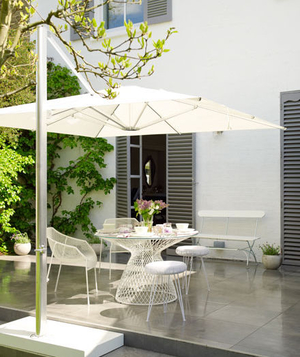 White Table, Chairs, And Parasol On Outdoor Patio